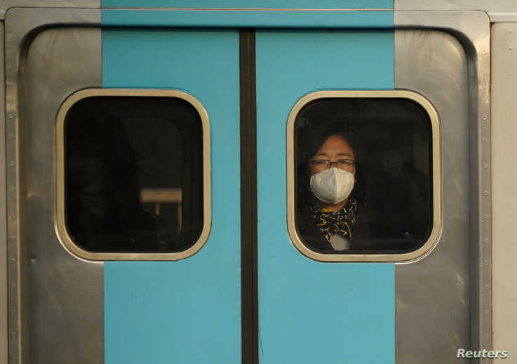 A woman wearing a mask to prevent contracting the coronavirus rides on a subway in Seoul, South Korea, February 20, 2020…