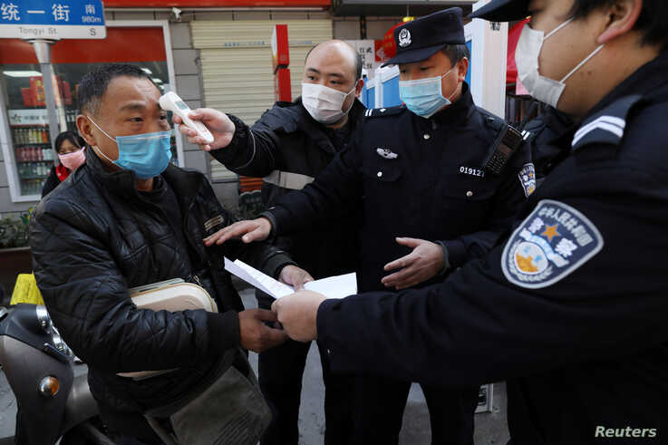 A community worker measures the body temperature of a man as police officers inspect his documents at a checkpoint set up at an…