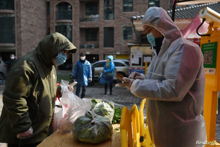 A resident collects vegetables purchased through group orders at the entrance of a residential compound in Wuhan, the epicentre…