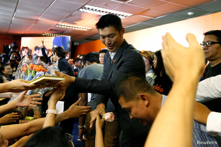 Supporters give presents to Future Forward Party leader Thanathorn Juangroongruangkit as he arrives to give a speech, at the…