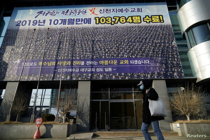 FILE PHOTO: A man wearing a mask to prevent contracting the coronavirus walks past a branch of the Shincheonji Church of Jesus…