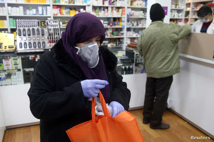 An Iranian woman wears a protective mask to prevent contracting coronavirus, as she is seen at a drug store in Tehran, Iran…