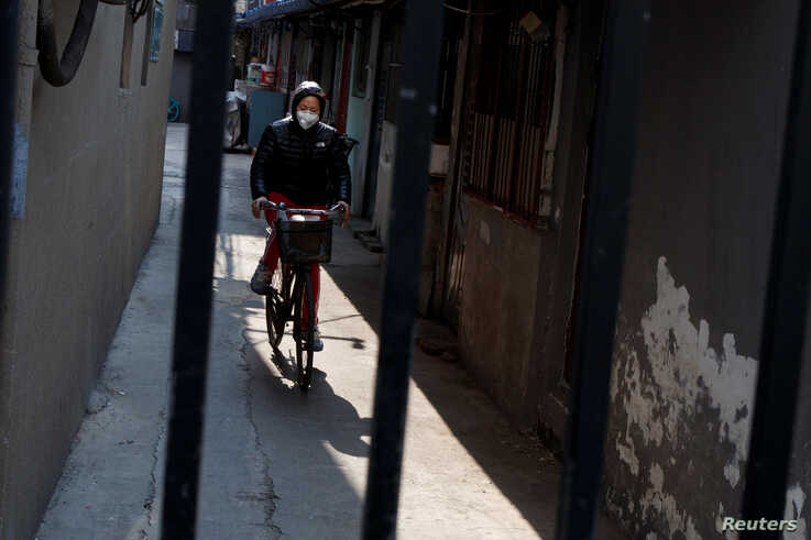 A woman wears a face mask as she rides a bicycle in a street in Beijing as the country is hit by an outbreak of the novel…