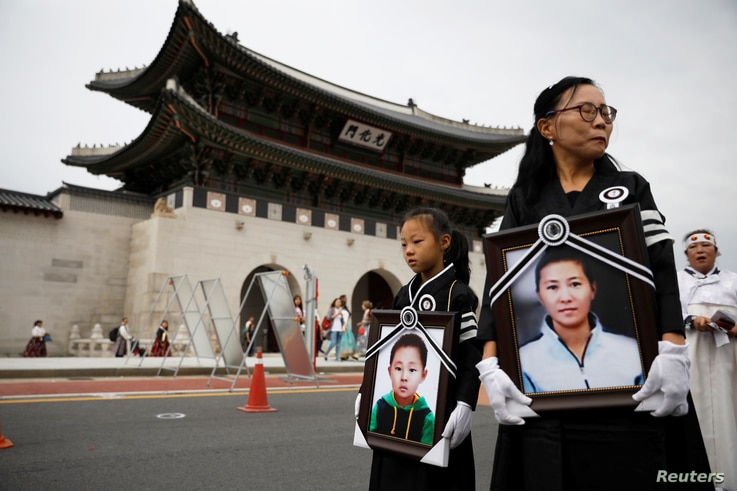 A girl and her North Korean defector mother hold portraits of a 42-year-old defector mother and  her 6-year-old son who were…