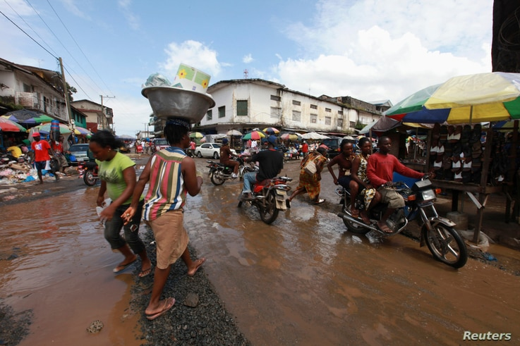 People and motorbikes pass along a junction at a market in the Waterside area of Monrovia October 13, 2011. REUTERS/Luc Gnago …