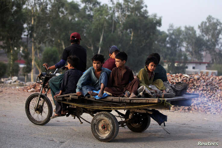 Boys from an Afghan refugee family, ride on a motorcycle cart, as they head to search for recyclables, in a low-income…