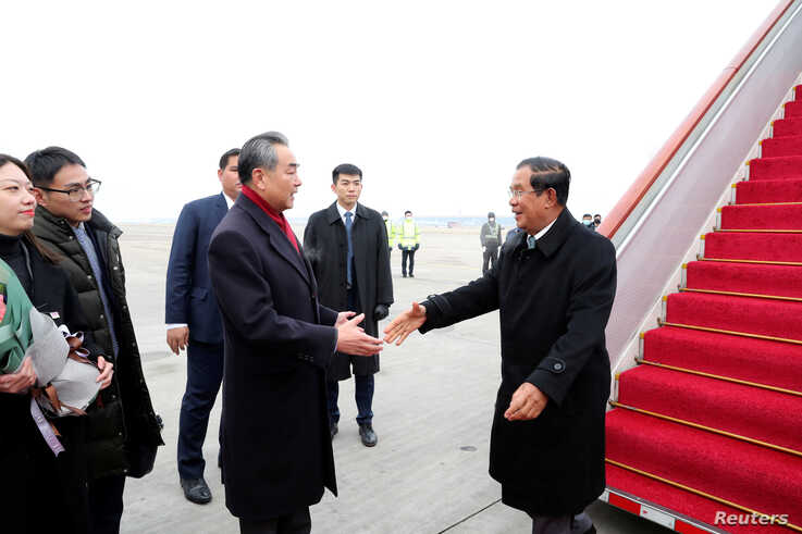 Chinese State Councilor and Foreign Minister Wang Yi welcomes Cambodian Prime Minister Hun Sen as he arrives at the Beijing…