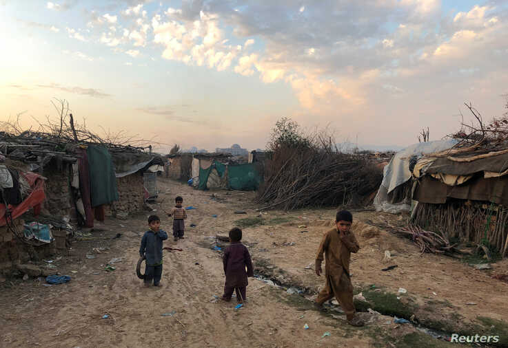 Children play outside their family's shelters at Afghan refugee camp in Islamabad, Pakistan February 13, 2020. Picture taken…