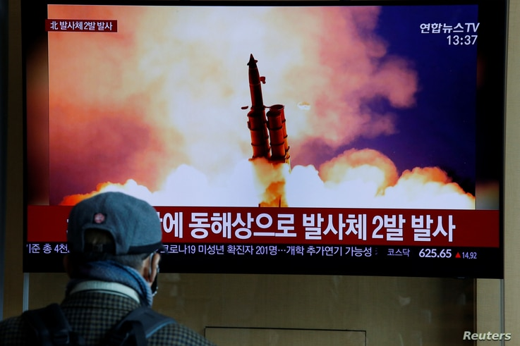 A man watches a TV showing a file picture for a news report on North Korea firing two unidentified projectiles, in Seoul, South…