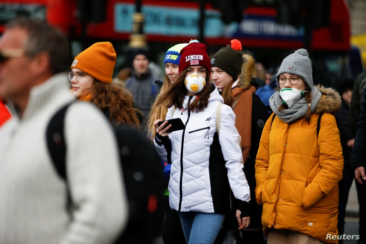 People are pictured wearing protective face masks in London, March 2, 2020.