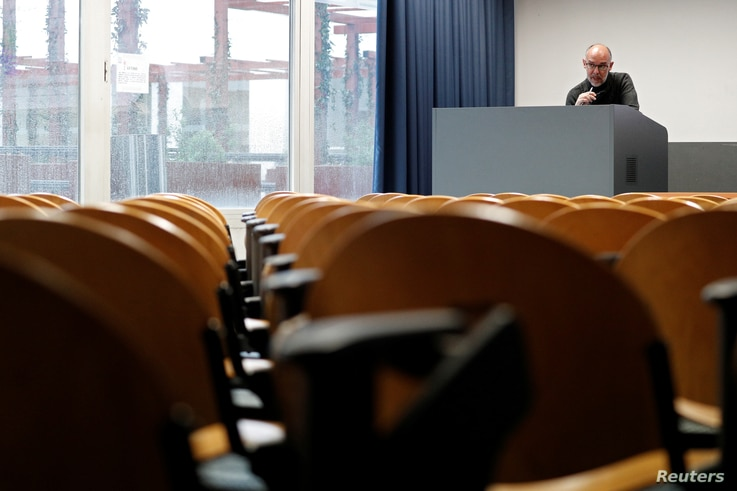 University Chemistry professor Luca De Gioia records his lesson in an empty class room to stream it online for his students at…