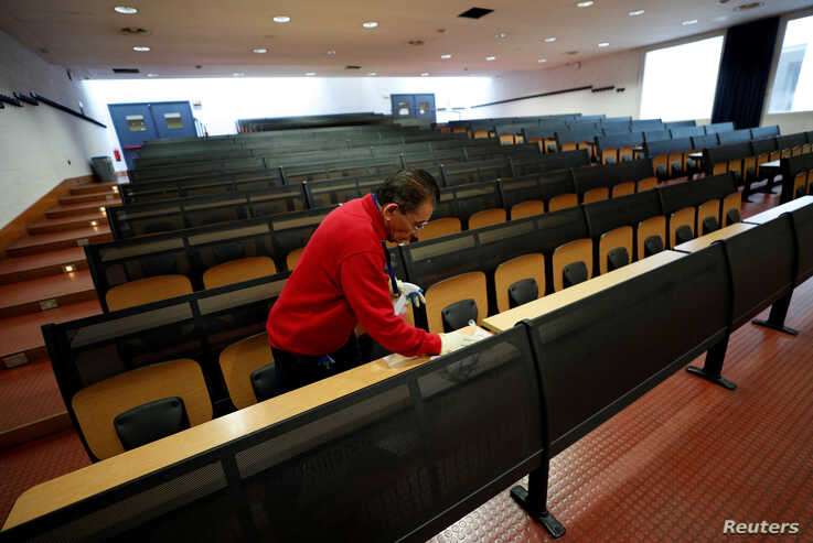 A man cleans an empty class room at the Bicocca University in Milan, Italy, March 2, 2020. Italian authorities have closed…