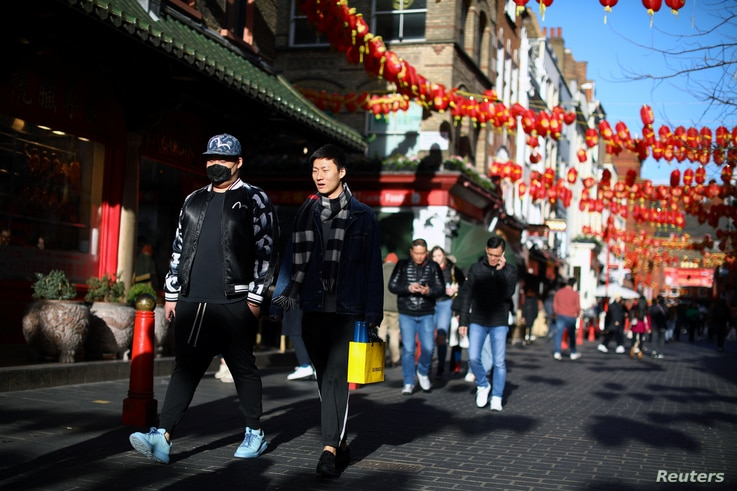A man wearing a protective face mask walks in Chinatown district, in London, Britain March 2, 2020. REUTERS/Tom Nicholson NO…