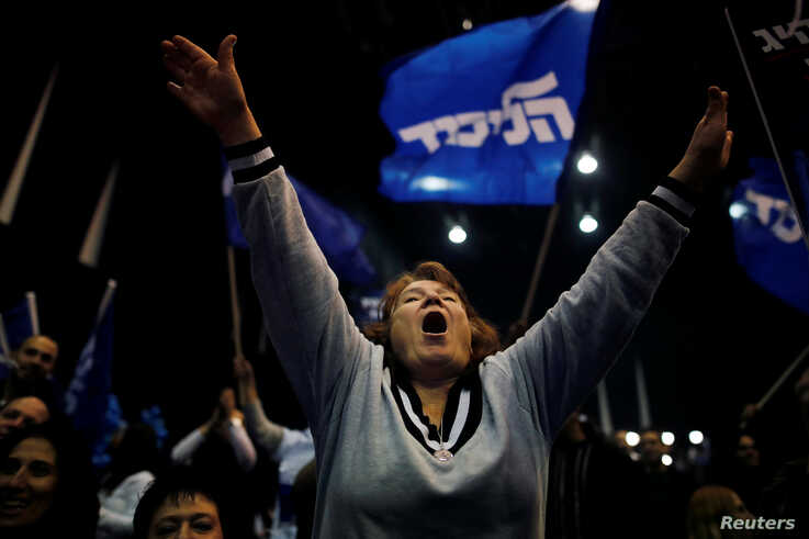 A supporter reacts following the announcement of exit polls in Israel's elections at Israeli Prime Minister Benjamin Netanyahu…