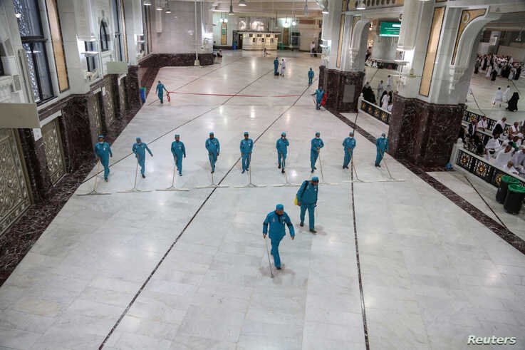 Cleaners wear protective face masks, following the outbreak of the coronavirus, as they swipe the floor at the Grand mosque in…