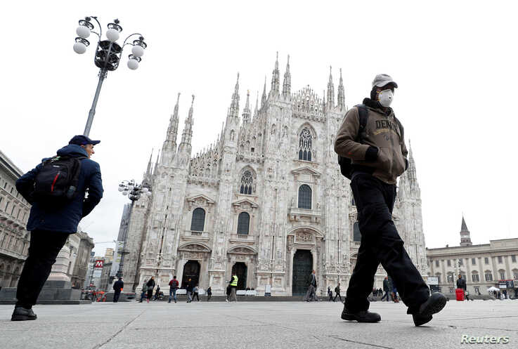 A man wearing a face mask walks past Piazza Duomo square after the government decree to close cinemas, schools and urge people…