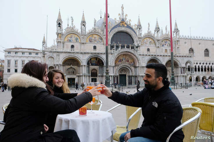 Venetians drink an aperol spritz in the Caffe Lavena at St Mark's Square, which has begun offering a free drink with every…