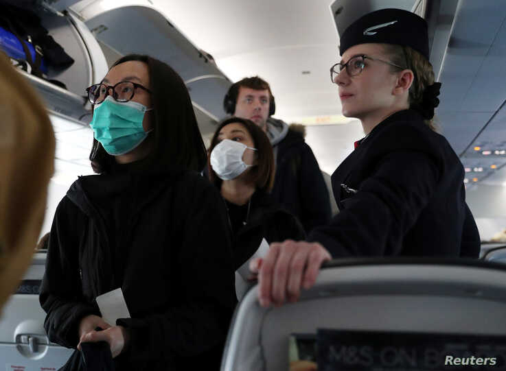 Passengers wear surgical masks as they board a British Airways flight from Terminal 5 at Heathrow Airport in London, Britain…