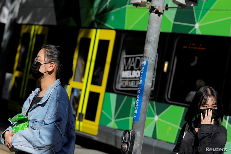 FILE PHOTO: People wearing face masks walk on Bourke Street after cases of the coronavirus were confirmed in Melbourne,…