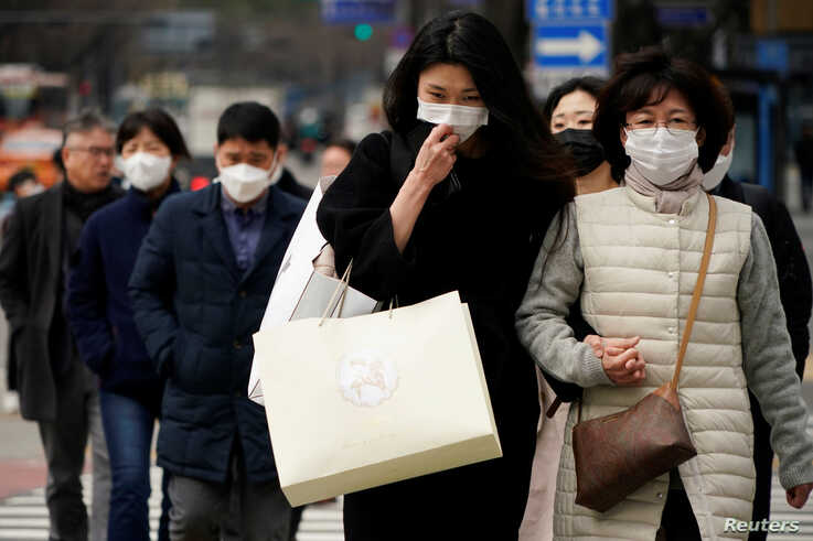 Pedestrians wearing masks to prevent contracting the coronavirus walk on a zebra crossing in Seoul, South Korea, March 12, 2020…