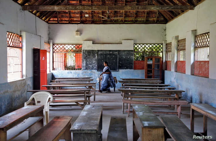 A staff member walks inside an empty classroom of a school after Kerala state government ordered the closure of schools across…