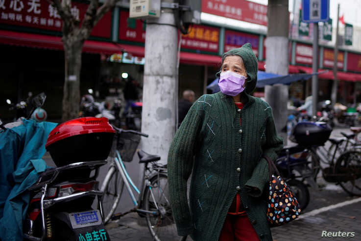 A woman wearing a protective face mask is seen at a residential community following an outbreak of coronavirus (COVID-19), in…