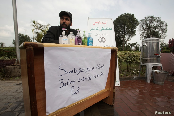 A government worker on a stall offers hand sanitizer as a preventive measure against coronavirus, to the people visiting a park…