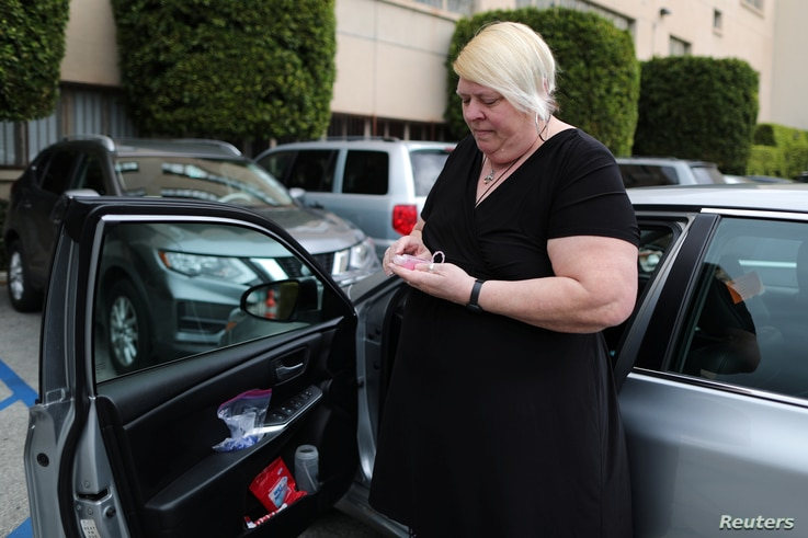 Uber and Lyft driver Tammie Jean Lane, 60, who had part of her lung removed after lung cancer, holds a bottle of hand sanitizer…