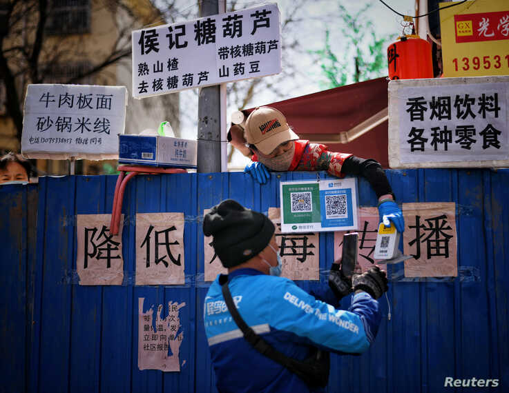 A deliveryman scans a QR code from an employee of a restaurant as he picks up food over barriers which has been set up to block…