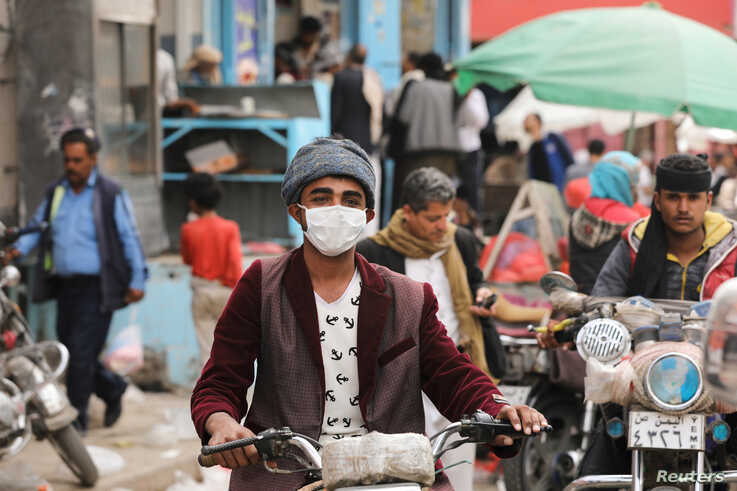 A man wears a protective face mask as he rides a motorcycle amid fears of the spread of the coronavirus disease (COVID-19) in…