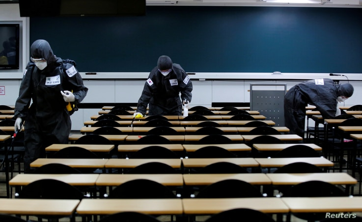 FILE PHOTO: South Korean soldiers clean desks with disinfectant in a classroom of a cram school for civil service exams,…