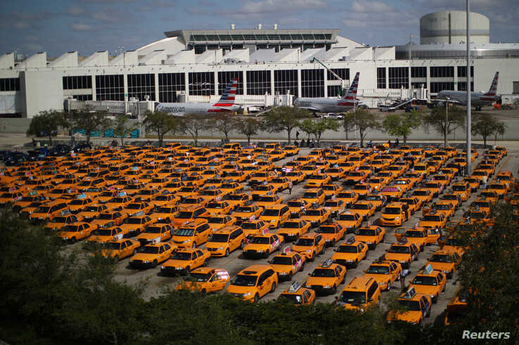 Taxis are seen at a parking lot of Miami International airport as air traffic and the tourism industry are affected by the…