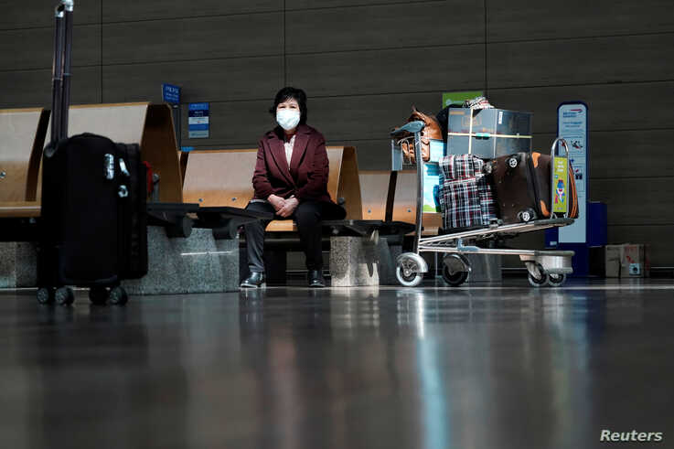 A woman wearing a mask to prevent contracting the coronavirus waits for her flight at Incheon International Airport in Incheon,…