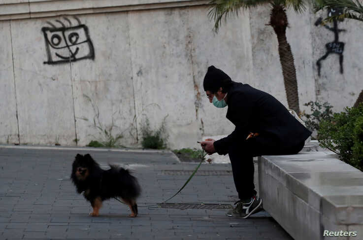 A man wearing a mask with his dog as Italy remains under a nationwide lockdown in a government decree that orders Italians to…