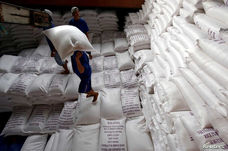 FILE PHOTO: Men load rice bags to a ship for export at a rice processing factory in Vietnam's southern Mekong delta, Vietnam…