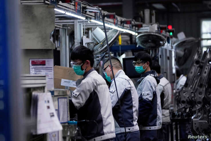 FILE PHOTO: Employees wearing face masks work on a car seat assembly line at Yanfeng Adient factory in Shanghai, China, as the…