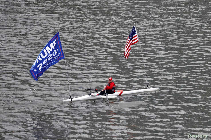 A person rows a boat flying a 'Trump 2020' banner and the United States flag during the outbreak of coronavirus disease (COVID…