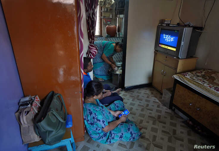 Suvarna Dinesh Rasal, 45, a nurse at Breach Candy Hospital Trust watches TV with her son Atharva Dinesh Rasal, 21, who works at…