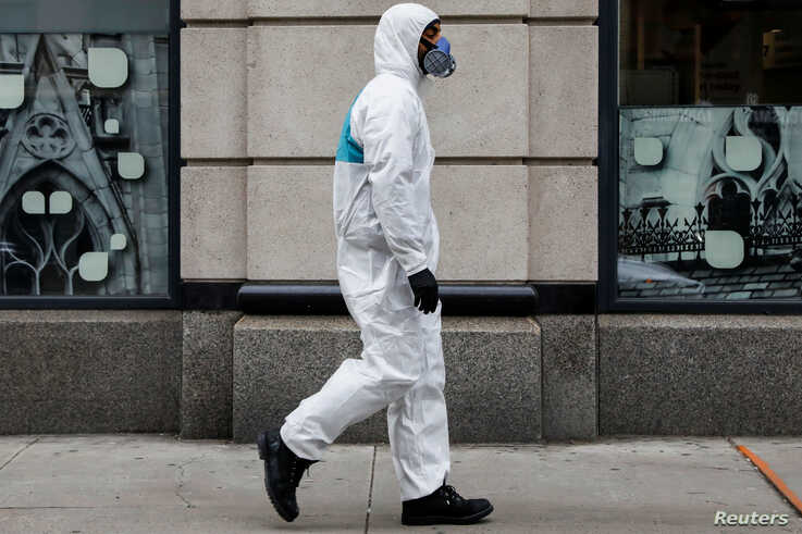 A man wears personal protective equipment (PPE) as he walks on First Avenue, during the coronavirus disease (COVID-19) outbreak…