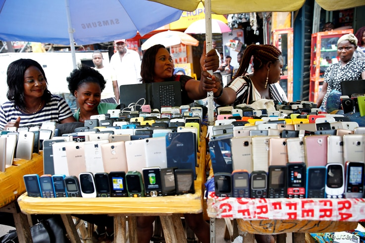 Women vendors display Nokia phone models for sale along with smartphones at the 'Computer Village' in Ikeja district in Nigeria…