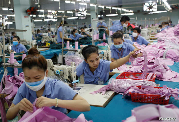 Labourers work at a garment assembly line of Thanh Cong textile, garment, investment and trading company in Ho Chi Minh city,…