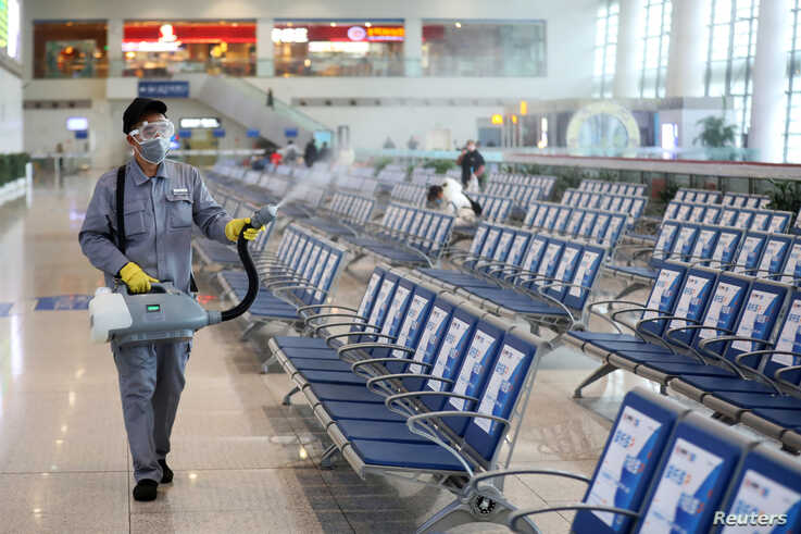 Workers in protective mask disinfects a waiting hall following the outbreak of a new coronavirus at the Nanjing Railway Station…