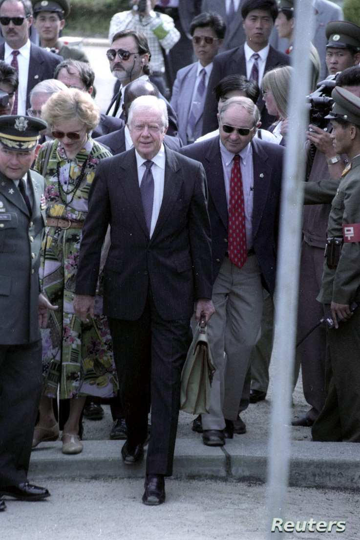 Former US President Jimmy Carter crosses the military demarcation line in Panmunjom from North to South Korea.   Former US…