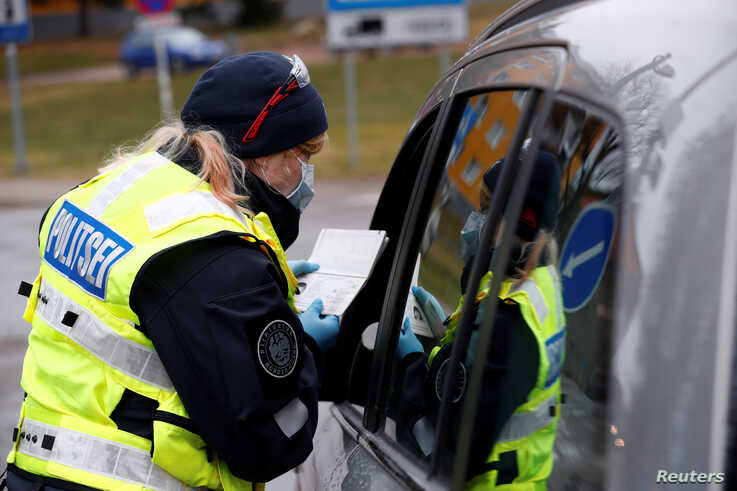 An Estonian police officer checks documents at the border crossing point as Estonia reintroduces border control and a ban to…