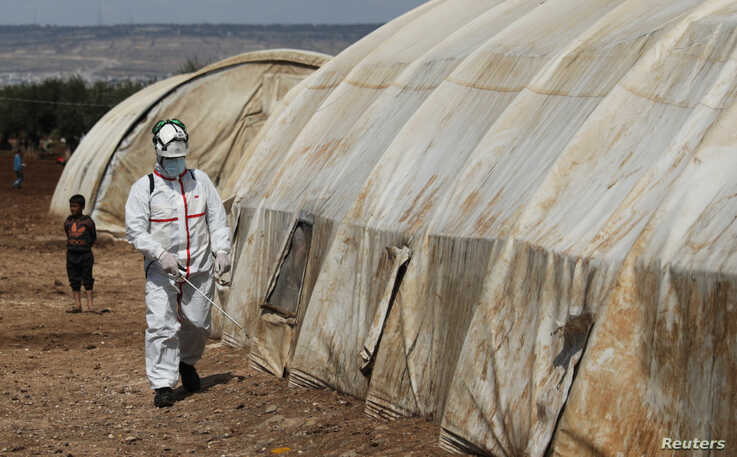 A member of the Syrian Civil defence sanitizes a tent at the Bab Al-Nour internally displaced persons camp, to prevent the…