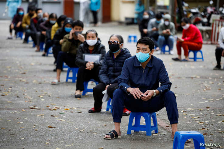 Residents wearing protective masks wait for coronavirus testing at a makeshift rapid testing center in Hanoi, Vietnam March 31,…