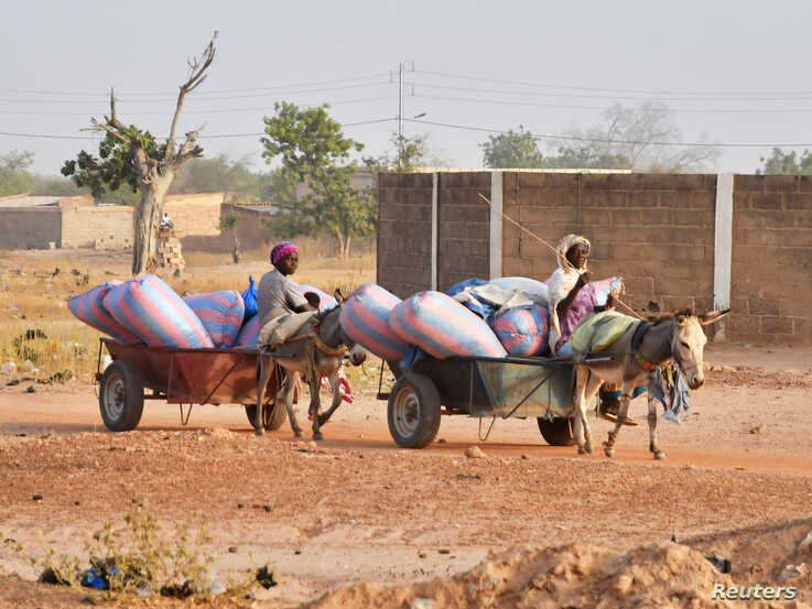 FILE PHOTO: Displaced women, who fled from attacks by armed militants in the town of Roffenega, ride donkey carts loaded with…