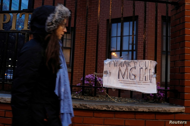 A pedestrian passes sign supporting the workers at Massachusetts General Hospital (MGH) near the hospital amid the coronavirus…
