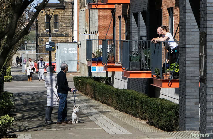 People are seen talking from their balcony with others walking their dog in Woolwich as the spread of the coronavirus disease …