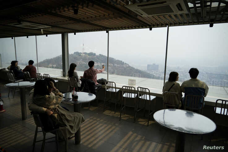 Couples enjoy the view while practicing social distancing during the global spread of the coronavirus disease (COVID-19), at an…